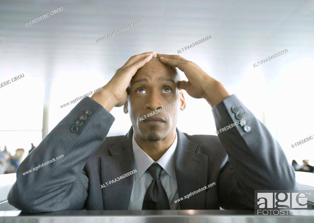 Stock Photo: Businessman looking up and holding head in airport.