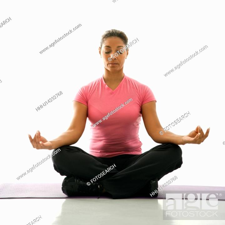 Stock Photo: Mid adult multiethnic woman sitting in lotus position on exercise mat with eyes closed and legs crossed.