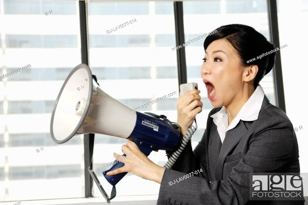 Stock Photo: Businesswoman yelling through a megaphone in an office.