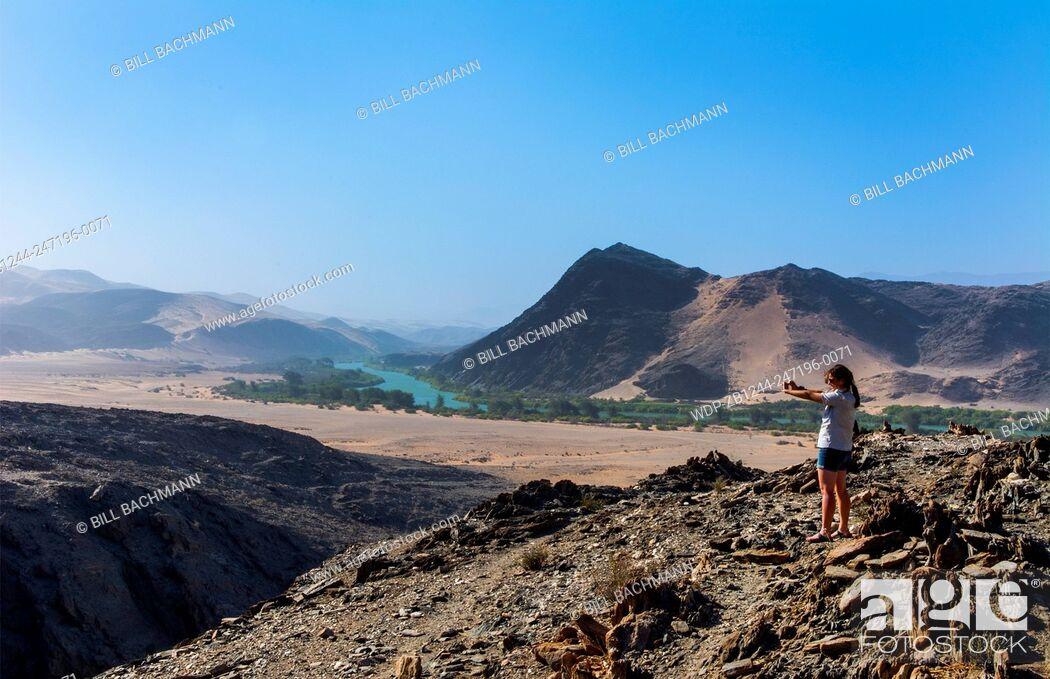 Imagen: Namibia Northern Desert of Namib Desertgreen tourist taking pictures of oasis river valley sand dunes of Hartmann Berge deserted land Hartmann Valley Marienflub.