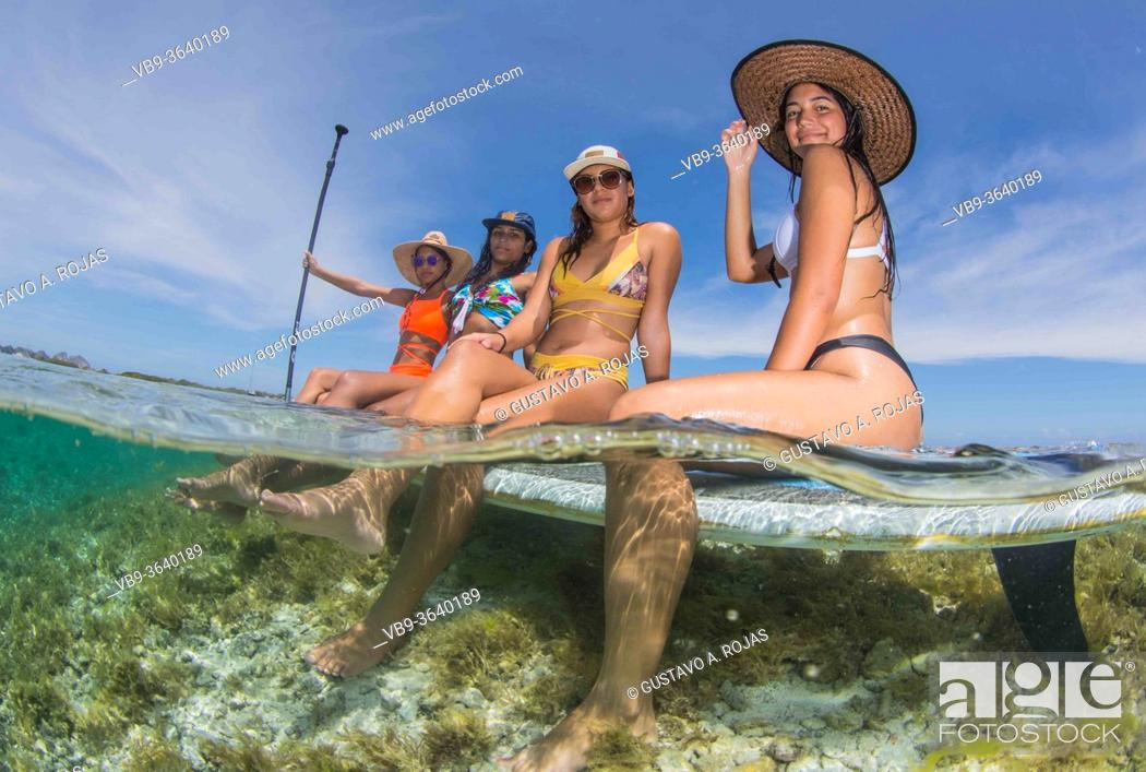 Stock Photo: Group friends women on paddle board together enjoyng sport activity at idyllic beach surrounded by turqoise water at Caribbean island.