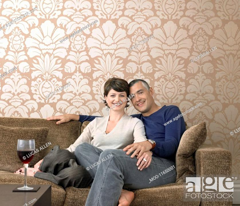 Stock Photo: Smiling couple relaxing on sofa in living room portrait.