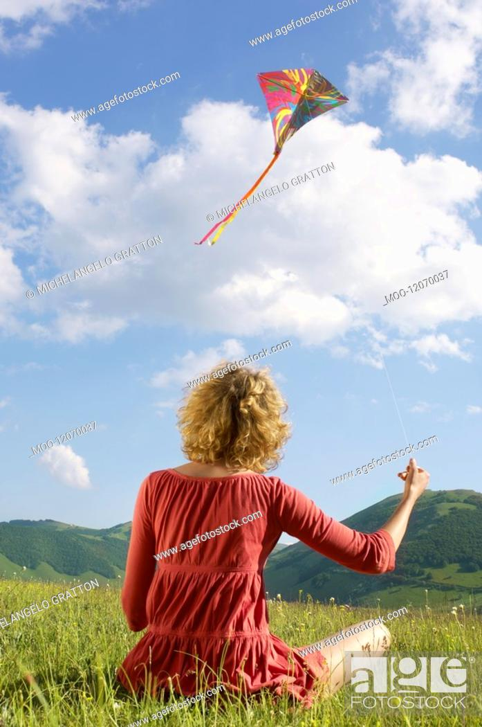 Stock Photo: Woman sitting in mountain field Flying Kite back view.