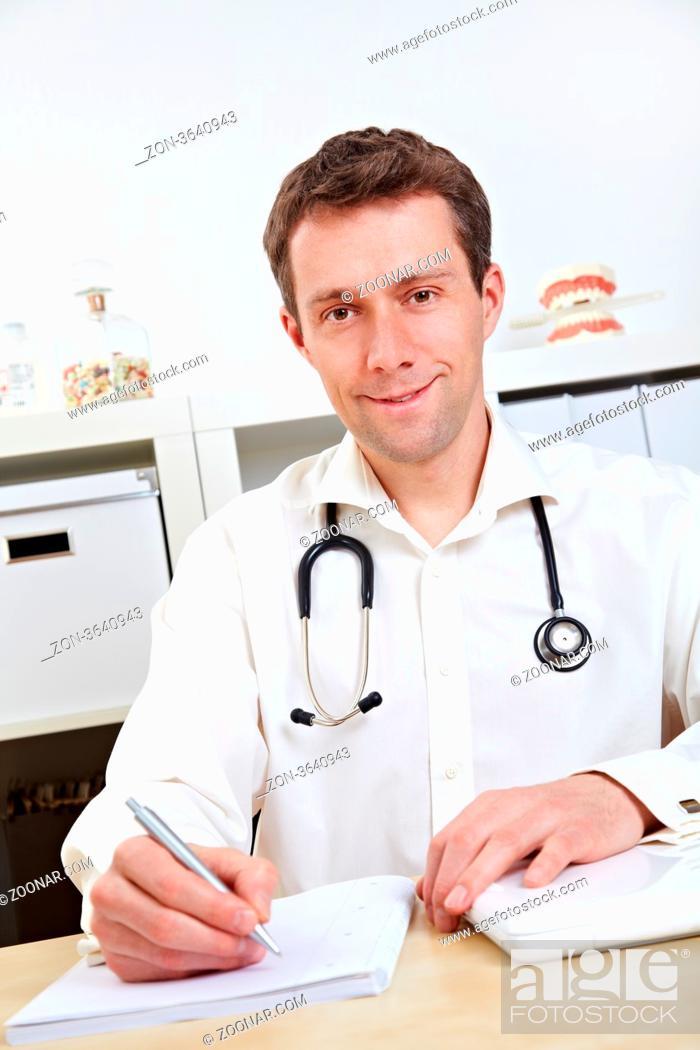 Stock Photo: Lächelnder Arzt hört vertrauensvoll zu und macht sich Notizen.