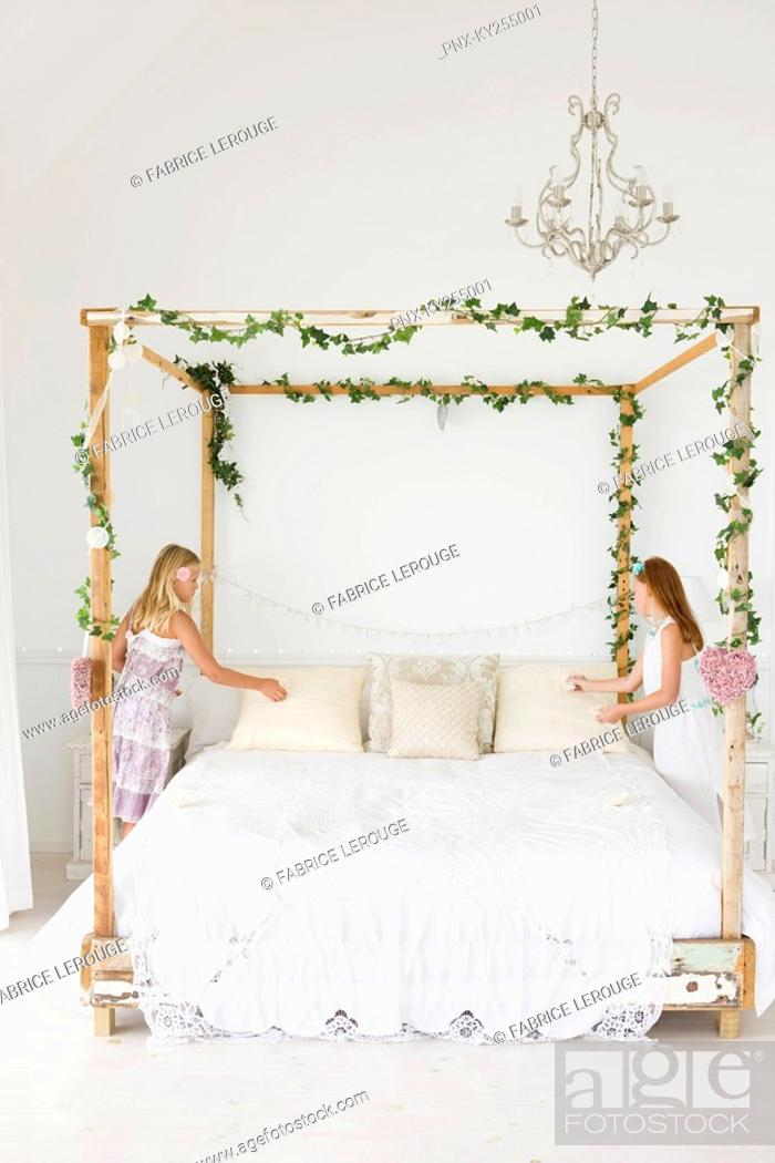 Stock Photo: Two girls decorating a bed.