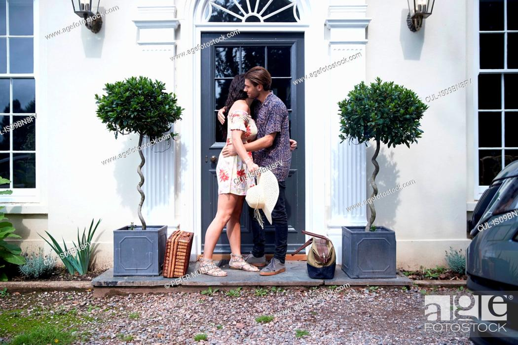 Stock Photo: Romantic couple hugging each other at hotel front door.