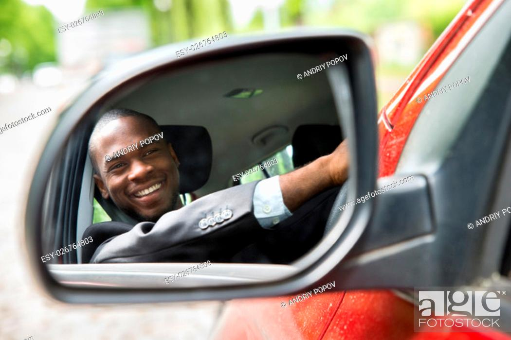 Stock Photo: Reflection Of Happy Young Businessman In Rear View Mirror Of Car.