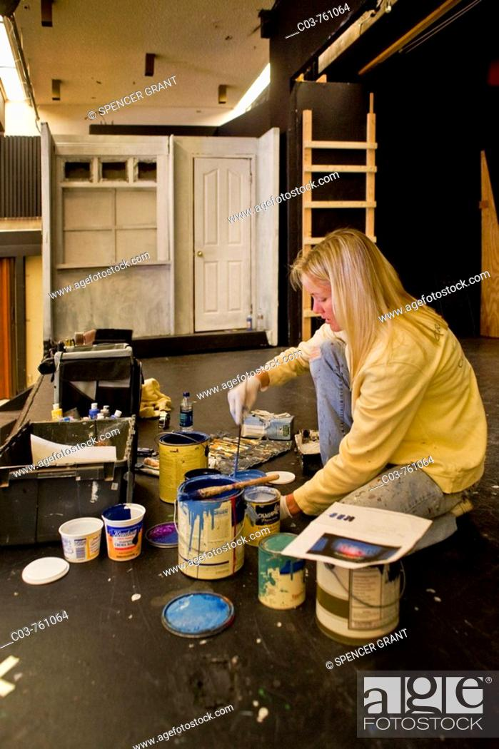 Photo de stock: A high school student mixes paint while building the set of a play in her school's theatre  Stagecraft is an elective course at the school.