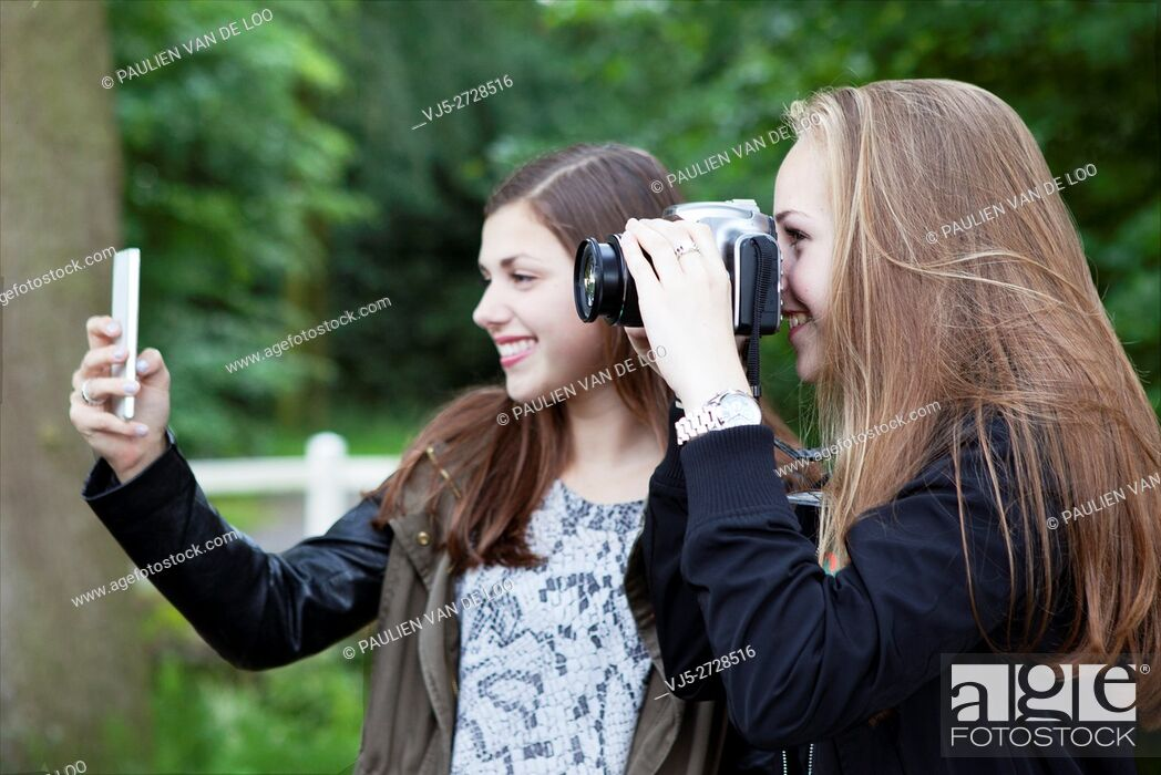 Stock Photo: Gemert, Netherlands, two teenage girls are taking pictures in a photo class.