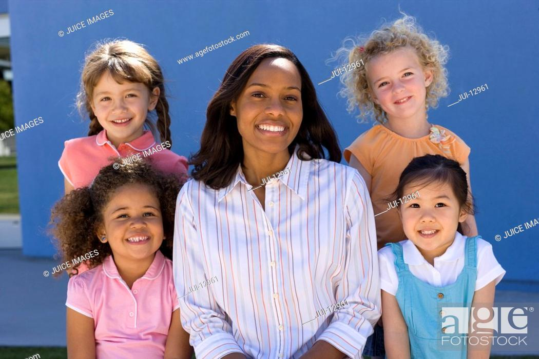 Stock Photo: Teacher and children 3-7, smiling, portrait.