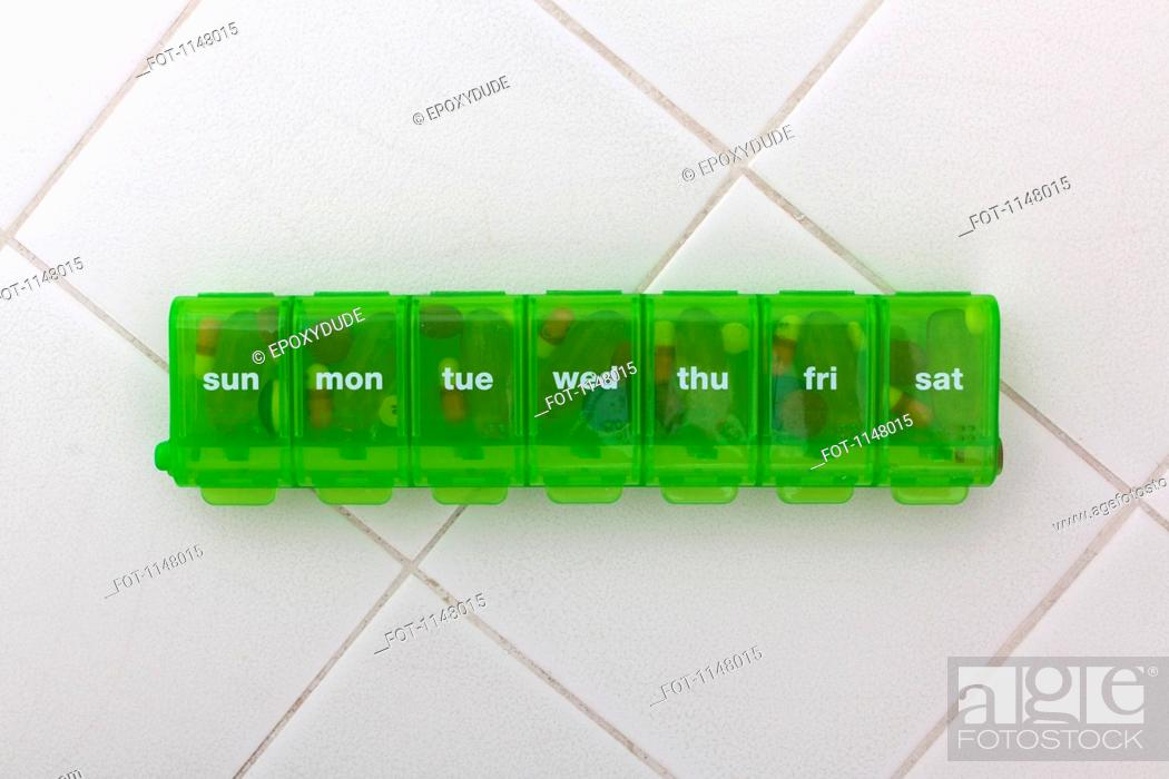 Stock Photo: A green pill organizer with the abbreviated days of the week.
