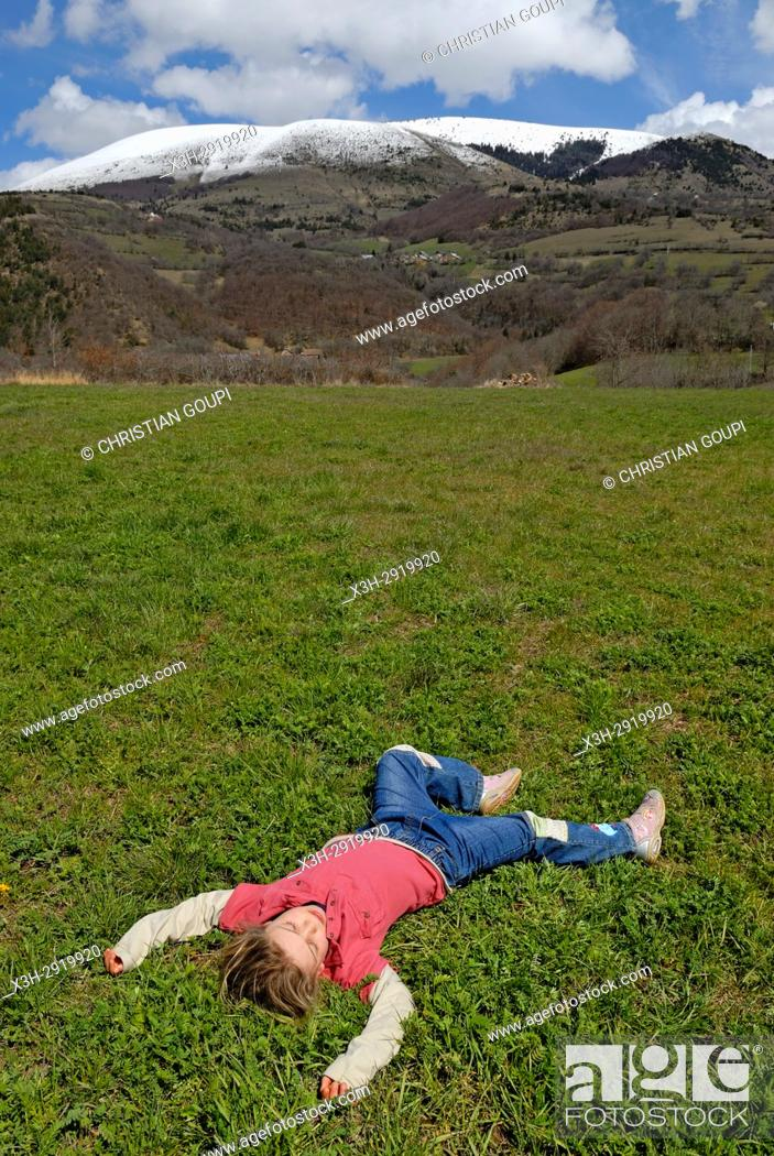 Stock Photo: little girl lying on the back in meadow, Alps, France, Europe.