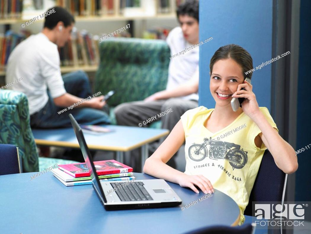 Stock Photo: Teenage using mobile phone sitting in library.
