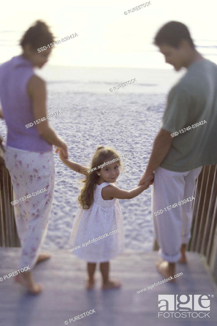 Stock Photo: Portrait of a girl holding her parents hands on the beach.