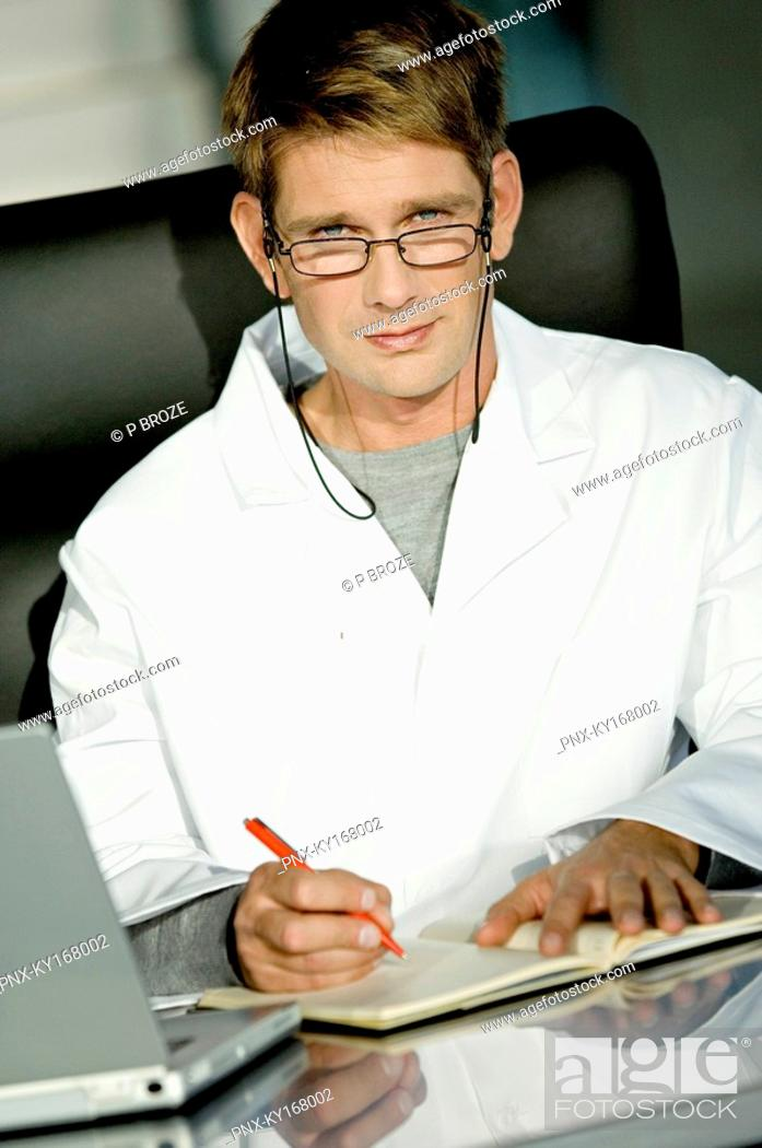 Stock Photo: Portrait of a male doctor sitting at a desk in his office and writing in a notebook.