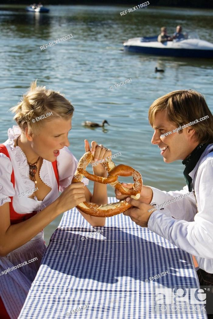 Stock Photo: Young couple in traditional Bavarian outfit, fighting over Pretzel, Munich.