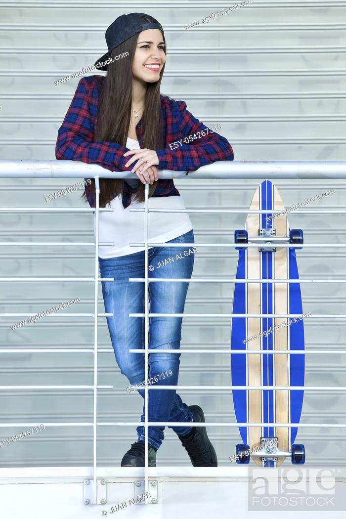 Stock Photo: Shot of young smiling female standing outside next to skate with legs and hands crossed.