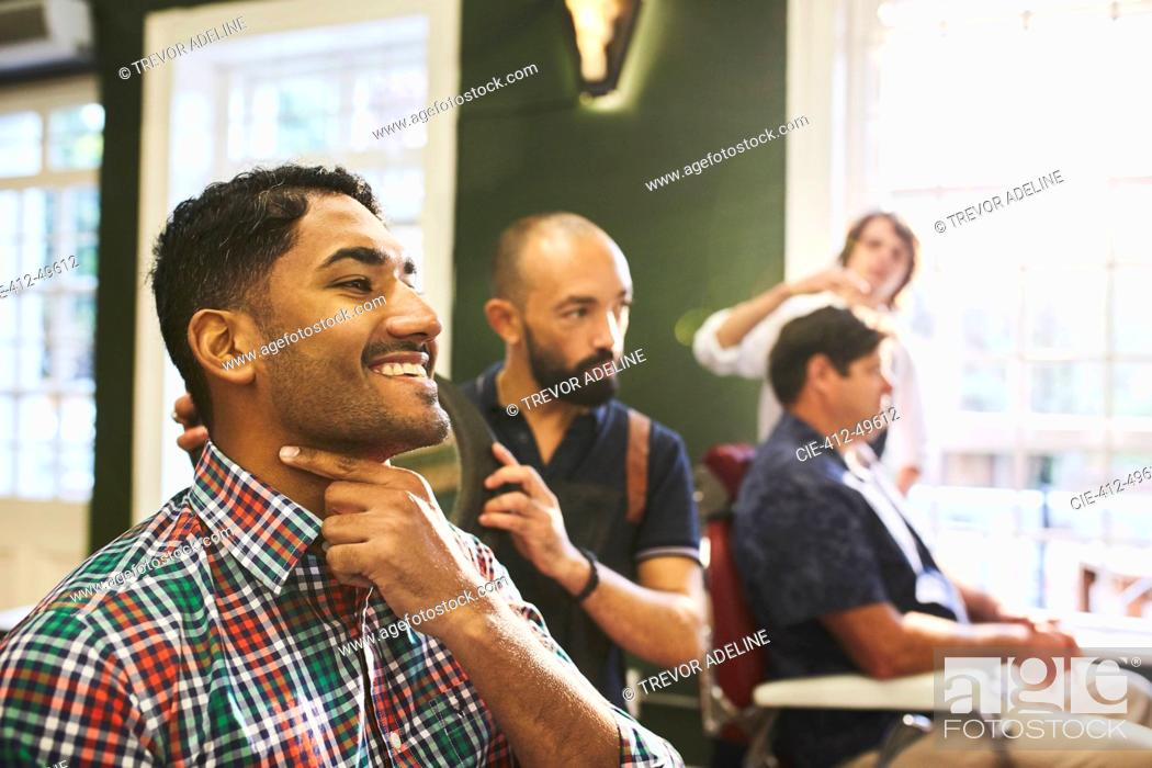 Stock Photo: Smiling male customer checking shaved face in barbershop.