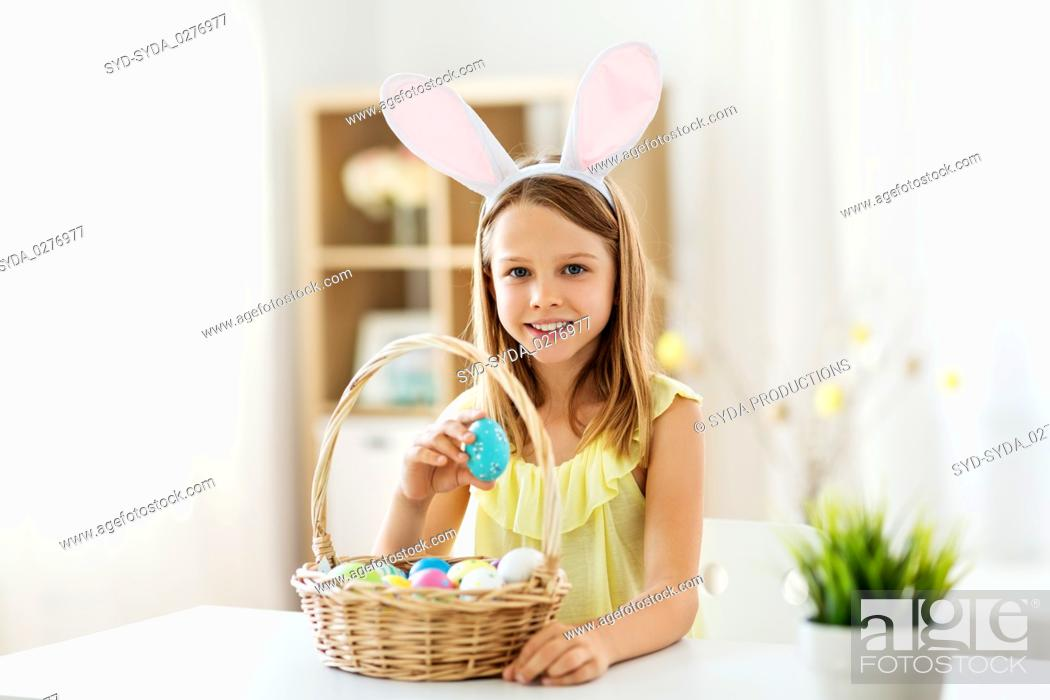 Stock Photo: happy girl with colored easter eggs at home.