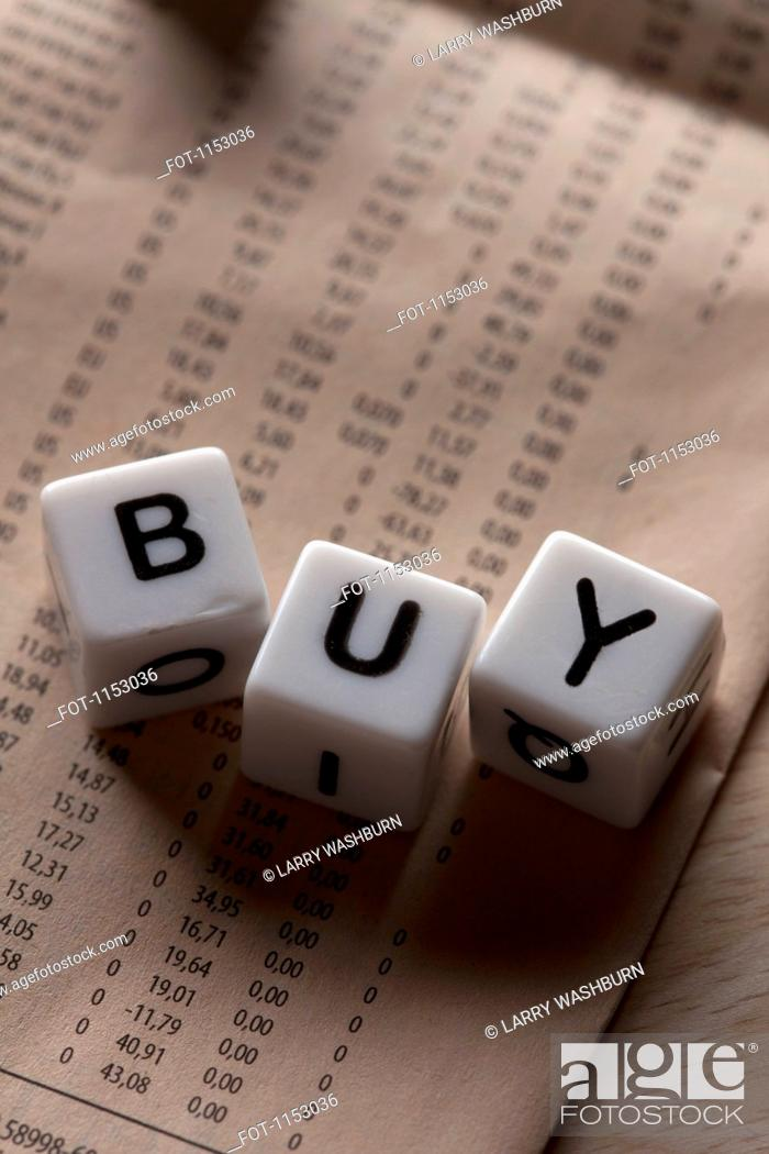 Stock Photo: Lettered cubes spelling BUY lying on top of a financial page.