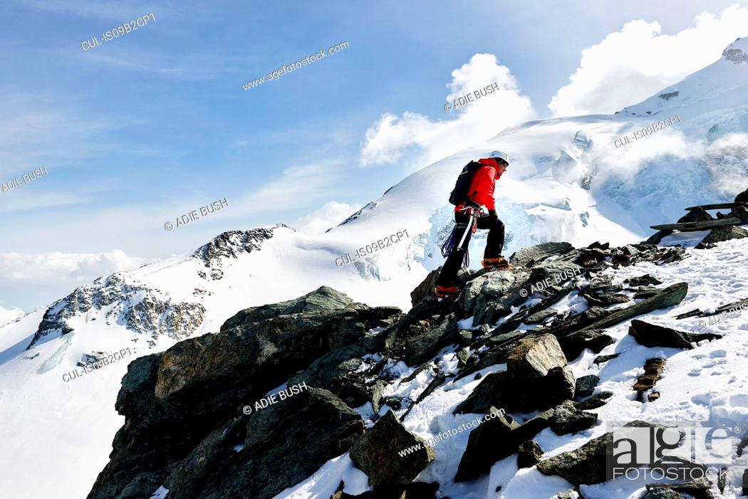 Imagen: Man climbing up snow covered mountain, Saas Fee, Switzerland.