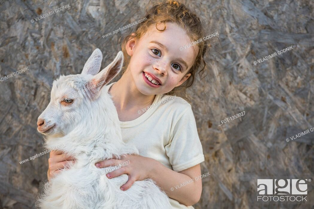 Stock Photo: Portrait of cute girl holding baby goat outdoors.