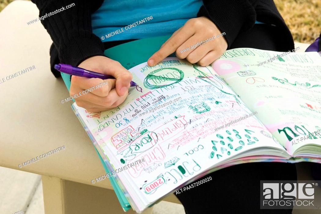 Stock Photo: Student writing in notebook illustrated with doodles.