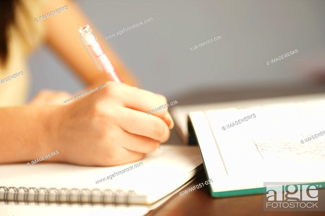 Stock Photo: Teenage girl 14-15 with book and pen, close-up.