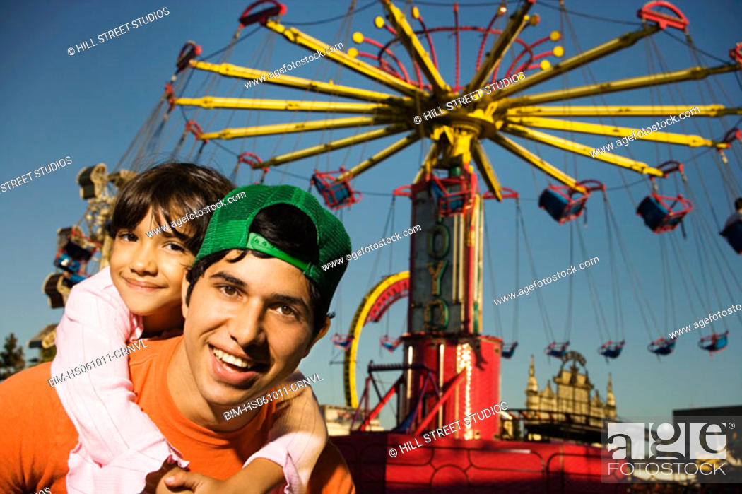 Imagen: Father giving his daughter a piggy-back ride at a carnival.
