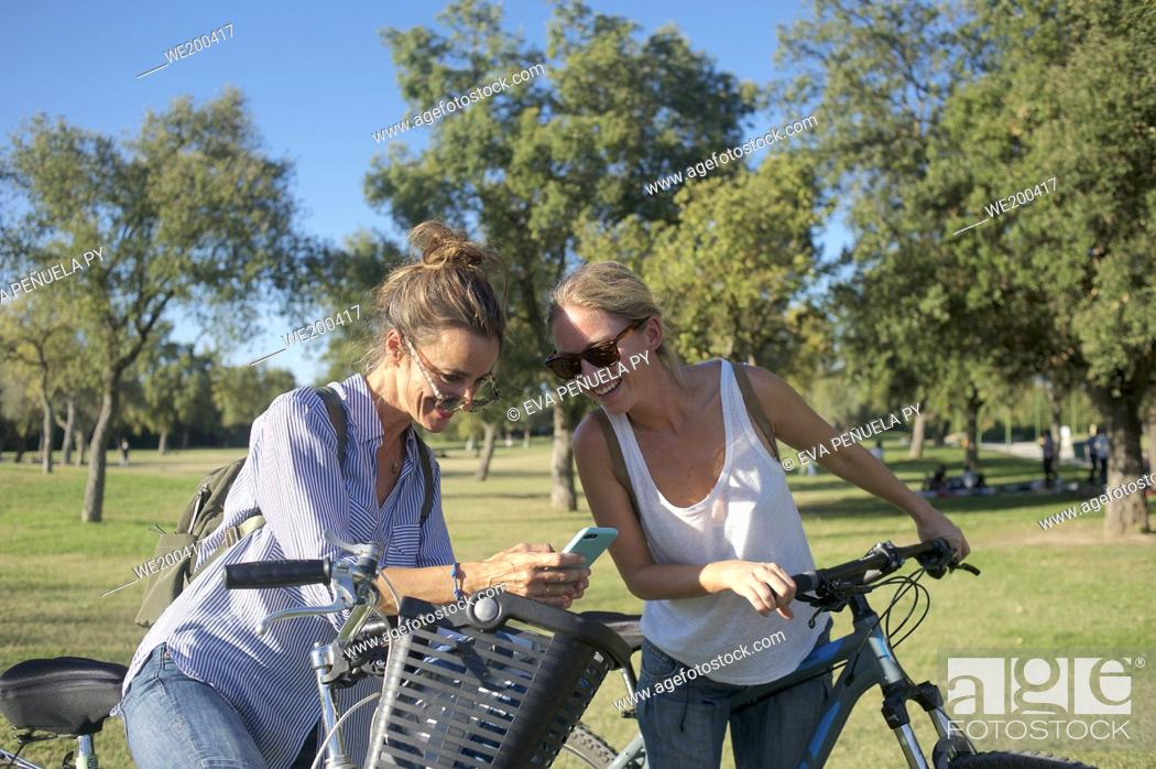 Stock Photo: Group of friends enjoying an afternoon on bicycles in the park....