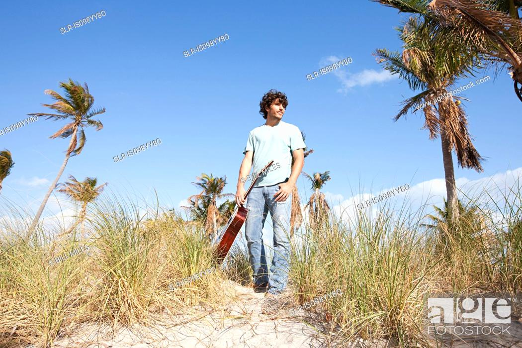 Stock Photo: Young man holding guitar on beach.