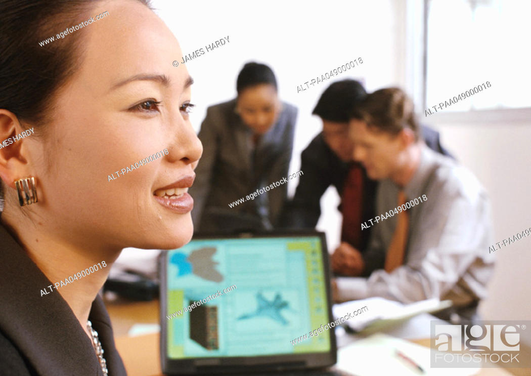 Stock Photo: Woman smiling, three people interacting in background.