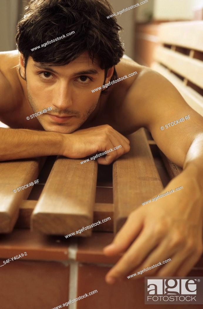Stock Photo: Darkhaired Man lying procumbently on a wooden Bench - Look - Allurement.