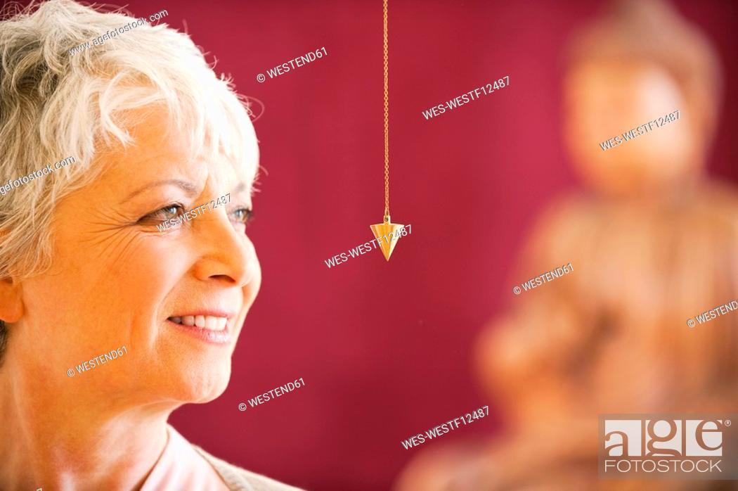 Stock Photo: Portrait of a senior woman holding pendulum.