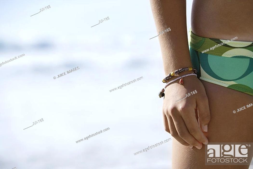 Stock Photo: Young woman standing on beach, wearing green bikini, mid-section, close-up, front view.