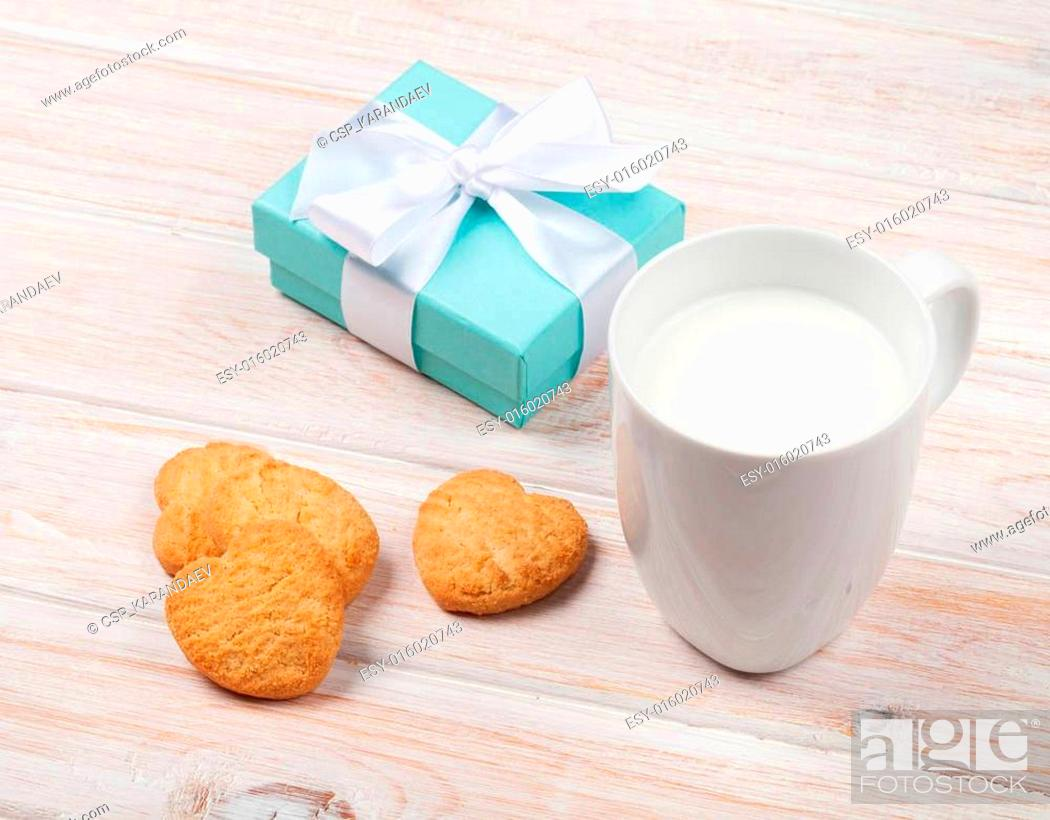 Stock Photo: Cup of milk, heart shaped cookies and gift box.