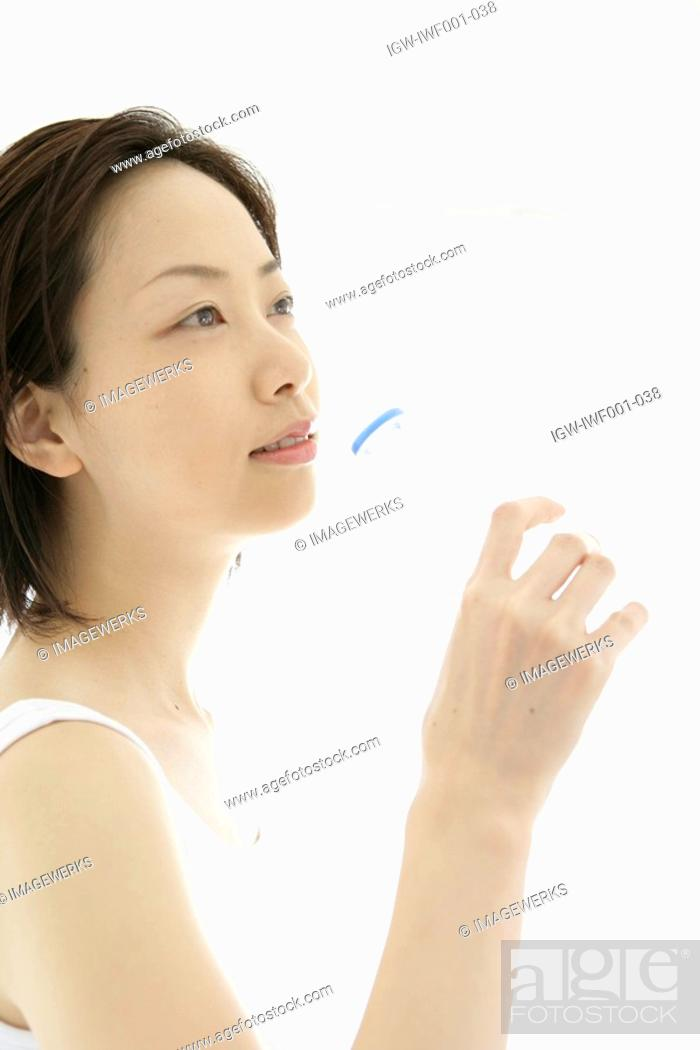Stock Photo: Side view of a young woman drinking water after her exercise.
