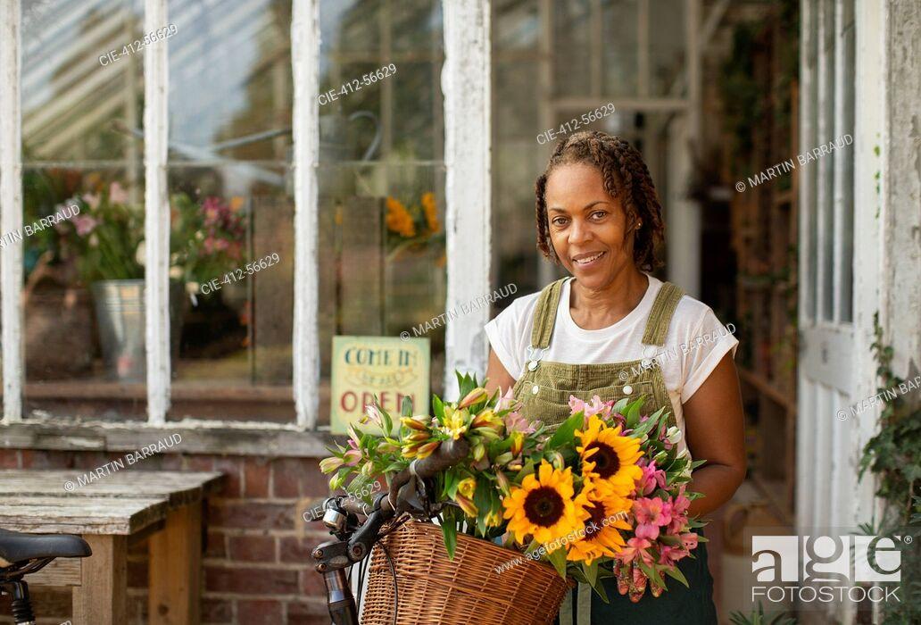 Stock Photo: Portrait female florist with flowers in bike basket outside shop.
