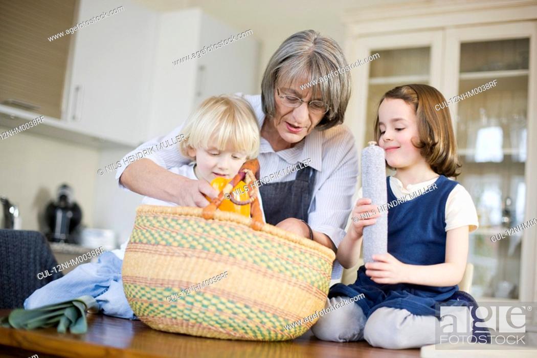 Stock Photo: grandmother and grandchildren packing.