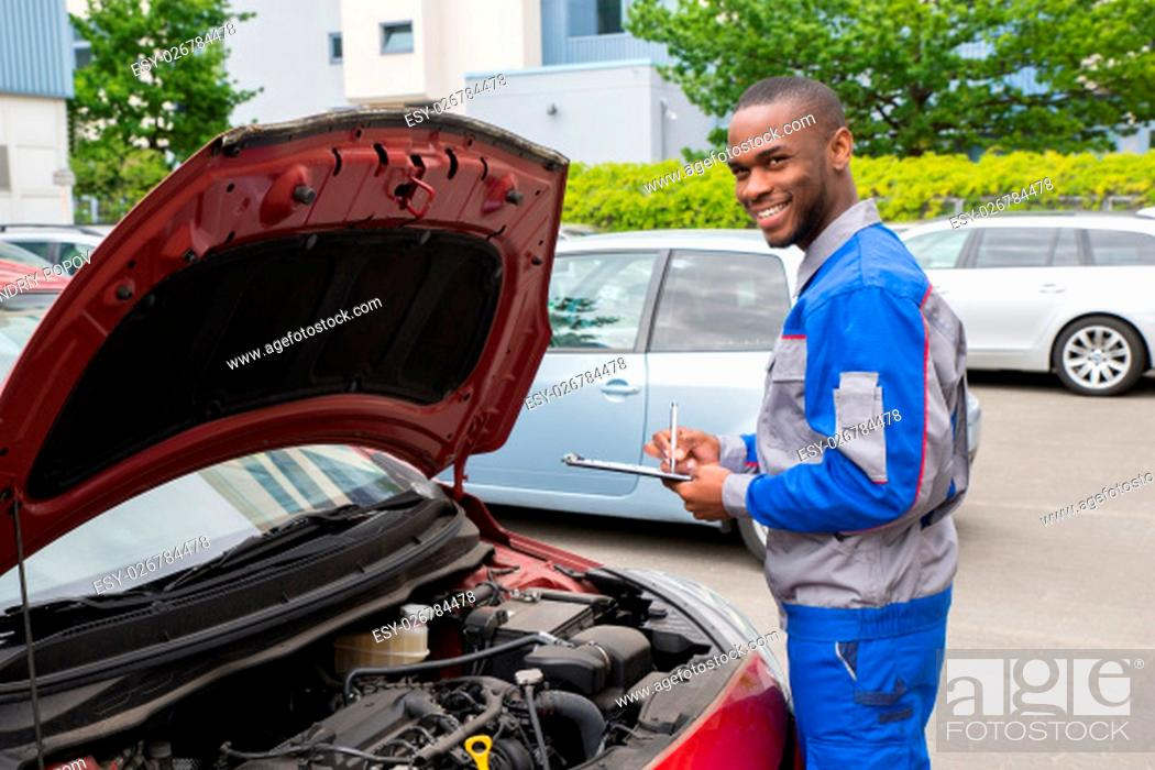 Stock Photo: Young African Mechanic Writing On Clipboard In Front Of Open Car Engine.