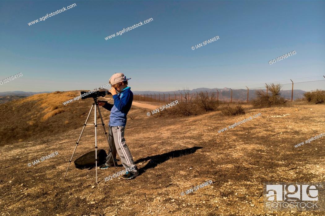 Stock Photo: Boy looking through telescope on tripod.