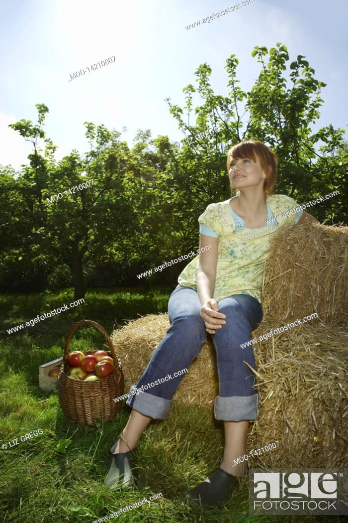 Stock Photo: Woman sitting on hay bales near orchard.