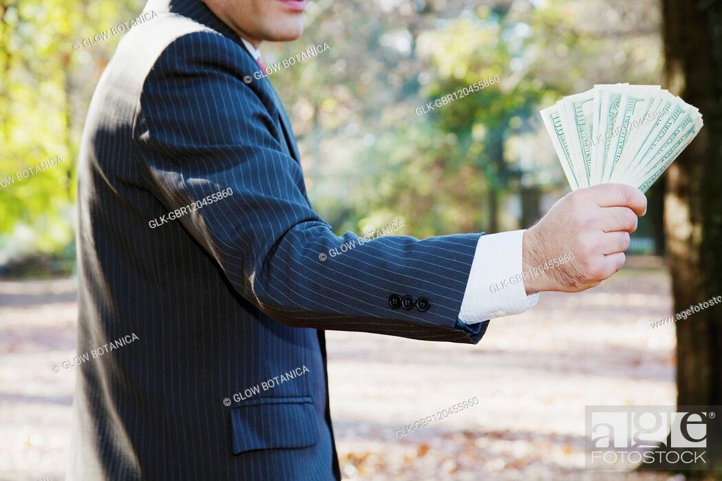 Stock Photo: Businessman holding currency notes.