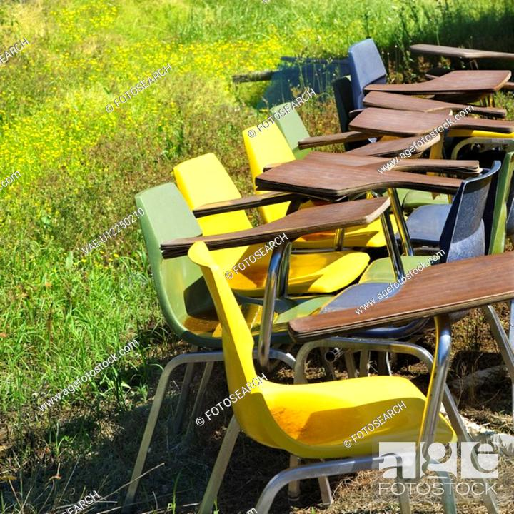 Stock Photo: Old school chairs in grassy field.