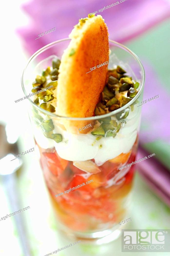 Stock Photo: peach, pear, pistachio and whipped cream dessert.