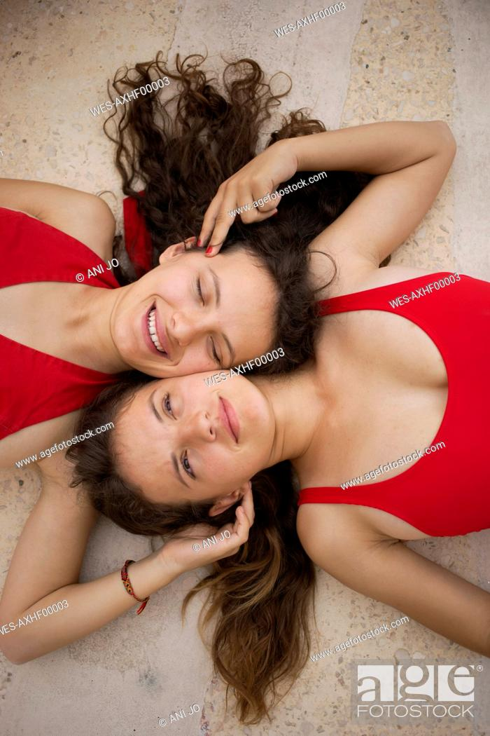 Stock Photo: Sisters wearing red clothing lying on floor.