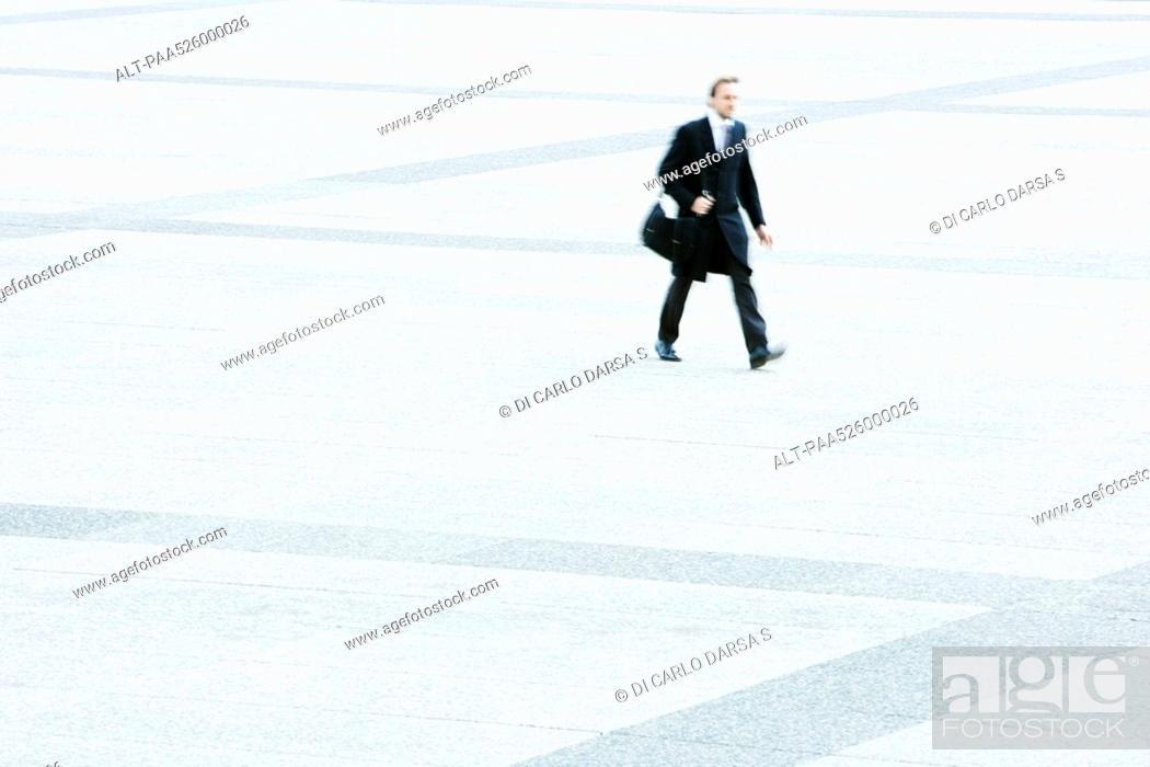 Stock Photo: Businessman hurrying across public square.