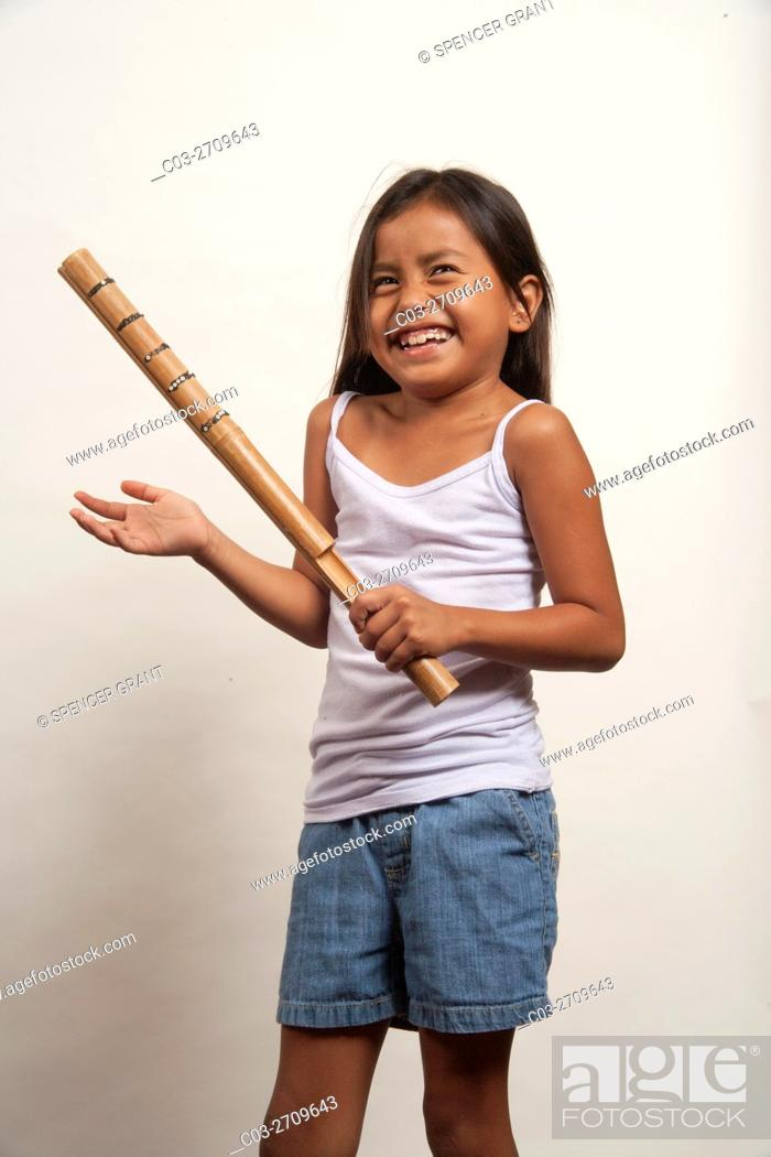 Stock Photo: A demonstrative Native American girl member of the Acjachemen tribe demonstrates the clapper stick, a primitive percussion musical instrument.