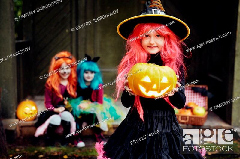 Stock Photo: Little Halloween witch holding jack-o-lantern on background of two girls.