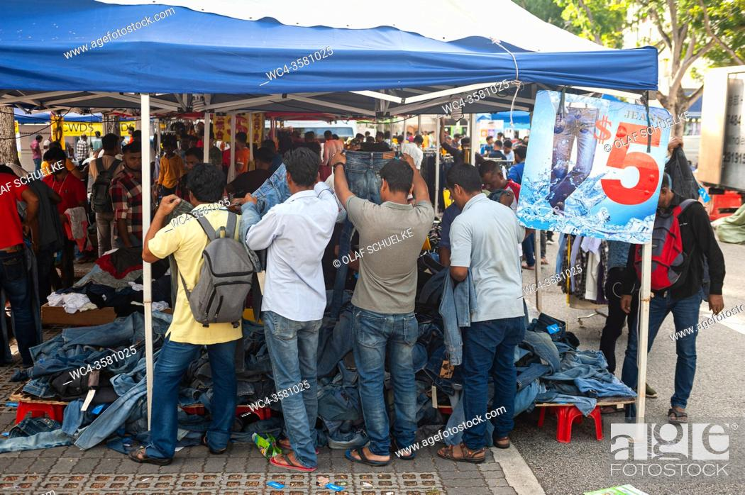 Stock Photo: Singapore, Republic of Singapore, Asia - Men of South Asian origin rummage for trousers and blue jeans at a street stall in Little India.